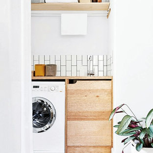 Photo of a small scandi single-wall utility room in Melbourne with a built-in sink, flat-panel cabinets, medium wood cabinets, wood worktops, white walls, painted wood flooring, a side by side washer and dryer, white floors and beige worktops.