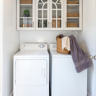 Dedicated laundry room - small transitional single-wall porcelain tile and gray floor dedicated laundry room idea in Los Angeles with glass-front cabinets, white cabinets, white walls and a side-by-side washer/dryer