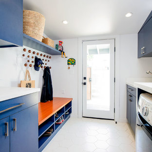 This is an example of a midcentury galley utility room in Los Angeles with flat-panel cabinets, blue cabinets, white walls, a side-by-side washer and dryer, beige floor and white benchtop.
