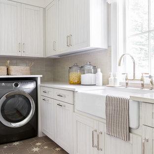 Ispirazione per una grande sala lavanderia classica con lavello stile country, ante con riquadro incassato, ante in legno chiaro, top in marmo, pareti beige, pavimento con piastrelle in ceramica, lavatrice e asciugatrice affiancate, pavimento marrone e top beige