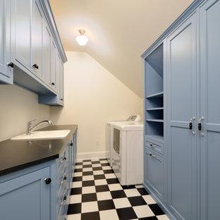 Inspiration för mellanstora klassiska parallella svart tvättstugor enbart för tvätt, med en nedsänkt diskho, skåp i shakerstil, blå skåp, vita väggar, klinkergolv i keramik och en tvättmaskin och torktumlare bredvid varandra