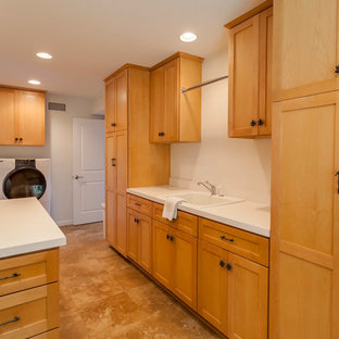 This is an example of a large galley utility room in Los Angeles with a drop-in sink, recessed-panel cabinets, light wood cabinets, white walls, travertine floors, a side-by-side washer and dryer and beige floor.