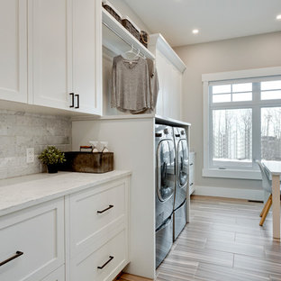 Large classic galley separated utility room in Calgary with shaker cabinets, white cabinets, quartz worktops, grey walls, porcelain flooring, a side by side washer and dryer, grey floors and white worktops.