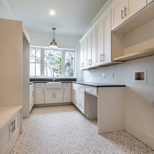 Design ideas for a medium sized country galley separated utility room in Orlando with a belfast sink, shaker cabinets, white cabinets, engineered stone countertops, white walls, ceramic flooring, a side by side washer and dryer, white floors and black worktops.