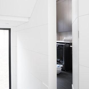 Modern inredning av en mellanstor vita parallell vitt tvättstuga enbart för tvätt och med garderob, med en integrerad diskho, släta luckor, skåp i mörkt trä, bänkskiva i kvartsit, vita väggar, klinkergolv i porslin och svart golv