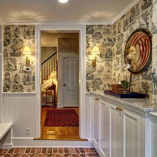 Exempel på ett mellanstort klassiskt linjärt grovkök, med skåp i shakerstil, vita skåp, beige väggar, tegelgolv, en tvättmaskin och torktumlare bredvid varandra och brunt golv