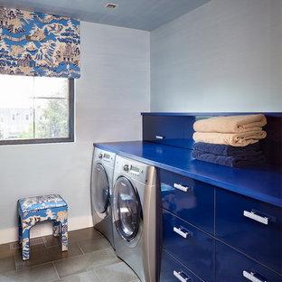ニューヨークのエクレクティックスタイルのおしゃれな洗濯室 (I型、フラットパネル扉のキャビネット、青いキャビネット、青い壁、左右配置の洗濯機・乾燥機、青いキッチンカウンター) の写真