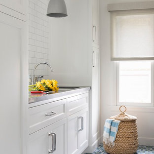Mid-sized transitional utility room in Los Angeles with an undermount sink, white cabinets, white walls, ceramic floors, multi-coloured floor, recessed-panel cabinets and grey benchtop.