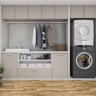 Bild på en mellanstor linjär tvättstuga, med en tvättpelare, målat trägolv och brunt golv