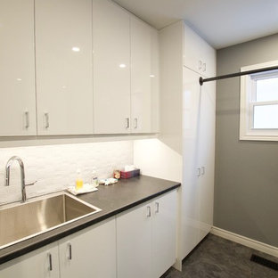 Photo of a medium sized contemporary galley separated utility room in Toronto with an utility sink, glass-front cabinets, white cabinets, laminate countertops, grey walls, vinyl flooring, a side by side washer and dryer, black floors and black worktops.