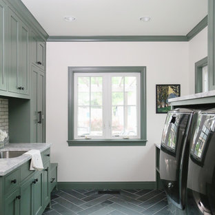 Photo of a mid-sized transitional galley utility room in Other with an undermount sink, shaker cabinets, green cabinets, marble benchtops, white walls, a side-by-side washer and dryer, grey benchtop, vinyl floors and grey floor.