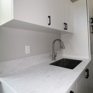 Large midcentury galley dedicated laundry room in Seattle with an undermount sink, flat-panel cabinets, white cabinets, solid surface benchtops, grey walls, concrete floors, a side-by-side washer and dryer, grey floor, white benchtop and vaulted.