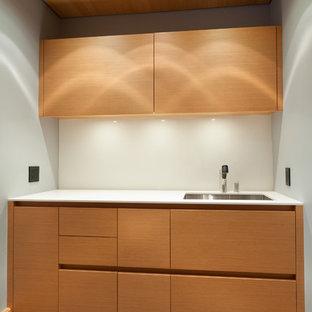 Immagine di una piccola sala lavanderia minimalista con lavello sottopiano, ante lisce, ante in legno chiaro, top in superficie solida, pareti grigie, pavimento in cemento, pavimento grigio e top bianco
