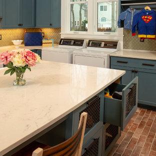 Exempel på en stor klassisk vita l-formad vitt tvättstuga enbart för tvätt, med en rustik diskho, skåp i shakerstil, blå skåp, bänkskiva i kvarts, gula väggar, klinkergolv i porslin, en tvättmaskin och torktumlare bredvid varandra och rött golv