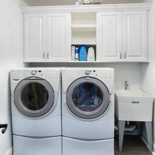 Idéer för att renovera en liten vintage tvättstuga, med en allbänk, luckor med upphöjd panel, vita skåp, vita väggar, klinkergolv i keramik och en tvättmaskin och torktumlare bredvid varandra