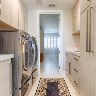 Example of a mid-sized trendy galley linoleum floor and beige floor dedicated laundry room design in Phoenix with flat-panel cabinets, light wood cabinets, beige walls, a side-by-side washer/dryer and a single-bowl sink
