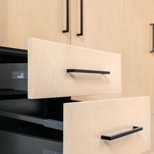 Ispirazione per una sala lavanderia minimalista di medie dimensioni con lavello sottopiano, ante lisce, ante in legno chiaro, top in quarzite, moquette, lavatrice e asciugatrice affiancate e pavimento grigio