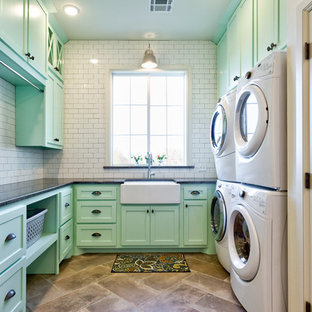 Cottage u-shaped brown floor dedicated laundry room photo in Oklahoma City with a farmhouse sink, shaker cabinets, green cabinets, a stacked washer/dryer and black countertops