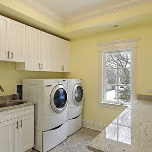 Esempio di una sala lavanderia classica di medie dimensioni con lavello sottopiano, ante in stile shaker, ante bianche, top in quarzo composito, pareti gialle, pavimento con piastrelle in ceramica, lavatrice e asciugatrice affiancate e pavimento multicolore