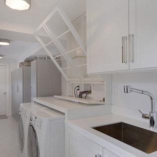 Foto på en stor funkis linjär tvättstuga enbart för tvätt, med en undermonterad diskho, luckor med infälld panel, vita skåp, bänkskiva i koppar, vita väggar, klinkergolv i porslin och en tvättmaskin och torktumlare bredvid varandra