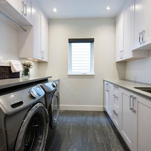Inspiration för mellanstora moderna parallella tvättstugor enbart för tvätt, med en undermonterad diskho, luckor med infälld panel, vita skåp, bänkskiva i kvarts, beige väggar, plywoodgolv och en tvättmaskin och torktumlare bredvid varandra