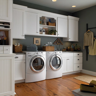 Inspiration for a mid-sized timeless single-wall light wood floor utility room remodel in San Diego with a drop-in sink, recessed-panel cabinets, white cabinets, granite countertops, gray walls and a side-by-side washer/dryer