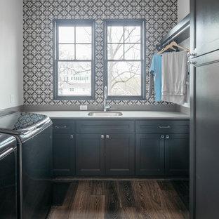 Exempel på en mellanstor klassisk vita parallell vitt tvättstuga enbart för tvätt, med en undermonterad diskho, luckor med infälld panel, svarta skåp, svarta väggar, mörkt trägolv, en tvättmaskin och torktumlare bredvid varandra och brunt golv