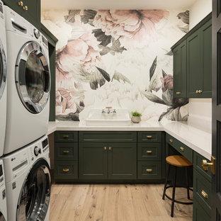 Foto di una grande sala lavanderia tradizionale con ante in stile shaker, ante verdi, pareti multicolore, parquet chiaro, top in quarzo composito, lavatrice e asciugatrice a colonna, pavimento beige, top bianco e lavello da incasso
