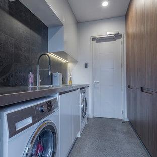Réalisation d'une grande buanderie parallèle minimaliste dédiée avec un évier intégré, un placard à porte plane, des portes de placard en bois sombre, un plan de travail en inox, un mur gris, béton au sol, des machines côte à côte et un sol gris.