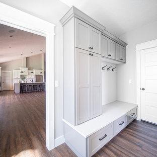 Bild på ett stort vintage vit parallellt vitt grovkök, med en undermonterad diskho, skåp i shakerstil, grå skåp, bänkskiva i kvarts, grå väggar, mellanmörkt trägolv, en tvättmaskin och torktumlare bredvid varandra och brunt golv