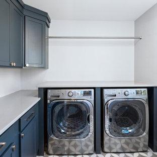 Aménagement d'une buanderie moderne en L dédiée et de taille moyenne avec un placard à porte shaker, des portes de placard bleues, un plan de travail en quartz modifié, un mur gris, des machines côte à côte, un sol gris et un plan de travail gris.