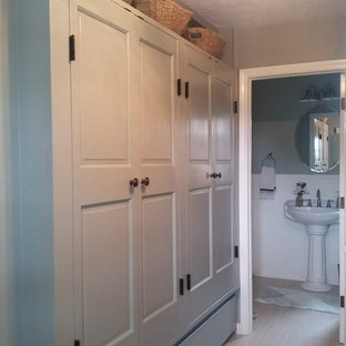 Photo of a medium sized country l-shaped utility room in Indianapolis with raised-panel cabinets, soapstone worktops, limestone flooring, a stacked washer and dryer, beige floors and black worktops.