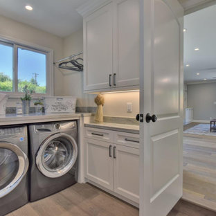 Photo of a small contemporary utility room in San Francisco with shaker cabinets, white cabinets, quartzite benchtops, grey walls, linoleum floors, a side-by-side washer and dryer, grey floor and green benchtop.