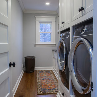 Photo of a traditional utility room in Other with marble worktops, grey walls, dark hardwood flooring, an integrated washer and dryer and black worktops.