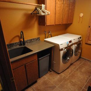 Diseño de cuarto de lavado de galera, bohemio, de tamaño medio, con fregadero bajoencimera, encimera de cuarzo compacto, paredes amarillas, suelo de baldosas de porcelana y lavadora y secadora juntas