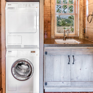 Design ideas for a mid-sized country single-wall dedicated laundry room in San Francisco with a single-bowl sink, light wood cabinets, copper benchtops, brown walls, ceramic floors and a stacked washer and dryer.