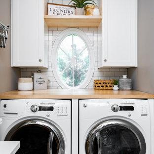 Inspiration för små maritima linjära flerfärgat grovkök, med en nedsänkt diskho, släta luckor, vita skåp, träbänkskiva, vitt stänkskydd, stänkskydd i tunnelbanekakel, grå väggar, klinkergolv i porslin, en tvättmaskin och torktumlare bredvid varandra och grått golv