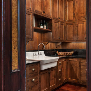 Photo of a large victorian l-shaped utility room in Other with a belfast sink, shaker cabinets, dark wood cabinets, composite countertops, brown walls, a side by side washer and dryer, dark hardwood flooring and brown floors.
