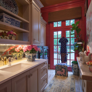 This is an example of a mid-sized traditional galley utility room in Atlanta with white cabinets, quartz benchtops, a side-by-side washer and dryer, an undermount sink, red walls, limestone floors and recessed-panel cabinets.