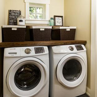 Exempel på en liten klassisk bruna linjär brunt tvättstuga enbart för tvätt, med träbänkskiva, gula väggar, klinkergolv i porslin, en tvättmaskin och torktumlare bredvid varandra och svart golv