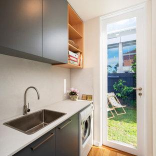 Idéer för små funkis parallella vitt grovkök med garderob, med en nedsänkt diskho, släta luckor, grå skåp, granitbänkskiva, vitt stänkskydd, beige väggar, mellanmörkt trägolv och brunt golv