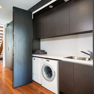Mid-sized modern single-wall laundry cupboard in Melbourne with a drop-in sink, quartz benchtops, white walls, medium hardwood floors, a side-by-side washer and dryer, flat-panel cabinets, white benchtop and brown cabinets.