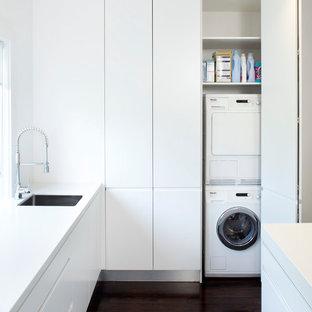 На фото: прачечные в стиле модернизм с белыми фасадами и со скрытой стиральной машиной