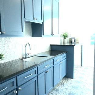 Idéer för stora maritima linjära grått tvättstugor enbart för tvätt, med en undermonterad diskho, skåp i shakerstil, blå skåp, bänkskiva i kvartsit, vita väggar, klinkergolv i keramik, en tvättmaskin och torktumlare bredvid varandra och blått golv