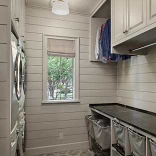 Photo of a medium sized classic galley separated utility room in Houston with an utility sink, raised-panel cabinets, grey cabinets, soapstone worktops, grey walls, concrete flooring, a stacked washer and dryer, grey floors and black worktops.