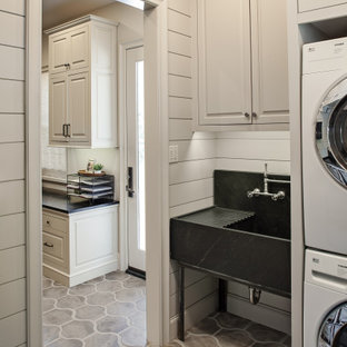 Example of a mid-sized transitional galley concrete floor and gray floor dedicated laundry room design in Houston with an utility sink, raised-panel cabinets, gray cabinets, soapstone countertops, gray walls, a stacked washer/dryer and black countertops