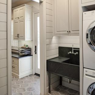 Immagine di una sala lavanderia classica di medie dimensioni con lavatoio, ante con bugna sagomata, ante grigie, top in saponaria, pareti grigie, pavimento in cemento, lavatrice e asciugatrice a colonna, pavimento grigio e top nero