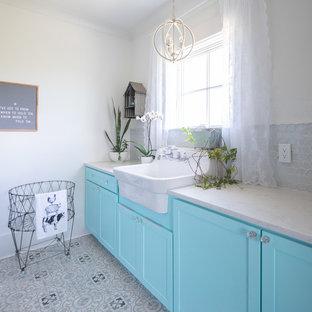 Foto di una sala lavanderia country di medie dimensioni con lavello stile country, ante in stile shaker, ante blu, top in quarzo composito, pareti bianche, pavimento con piastrelle in ceramica, lavatrice e asciugatrice affiancate, pavimento grigio e top bianco