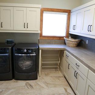 Inspiration för mellanstora moderna l-formade tvättstugor enbart för tvätt, med en tvättmaskin och torktumlare bredvid varandra, skåp i shakerstil, beige skåp, kaklad bänkskiva, beige väggar och travertin golv
