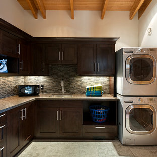 Design ideas for a large rustic l-shaped separated utility room in Vancouver with a submerged sink, shaker cabinets, dark wood cabinets, granite worktops, white walls, ceramic flooring, a stacked washer and dryer and grey floors.